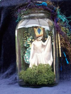 I found this lovely fairy in my aunts rose garden near the arbor. She is a real treasure. Her name is Madeline and she loves to be around people - a real delight!    Madeline is in a quart-sized Kerr Mason jar with air holes drilled in the top of the lid which is decorated with fibers, a skeleton key, and a vintage button. She is in a bed of reindeer moss to keep her comfortable.    Proud member of Old World Shoppes  Our members have a passion for old-fashioned, vintage, and Victorian arts…