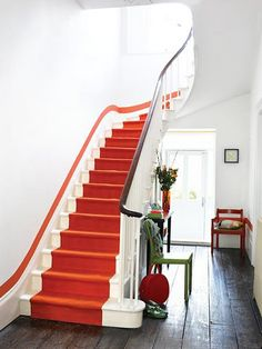 Une large bande de peinture colorée parcourant les escaliers comme un tapis en trompe-l'œil. Le tout souligné par une bande étroite de même couleur courant le long du mur.