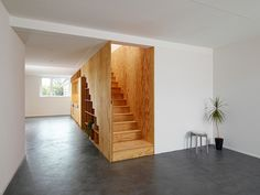 Beautiful multifunctional fixed furniture made from timber panelling into this plain white interior. I love how the space underneath the stairs has been divided into geometric shelves mimicking the shape of the stairs. Plywood Interior, Interior Stairs, Interior Architecture, Room Interior, Interior Design And Build, Apartment Interior Design, Modern Interior, Built In Furniture, Wooden Furniture
