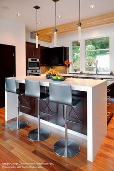 This modern kitchen involves tons of natural wood for a mixed contemporary feeling. White-wrapped upper island tier provides dining space, below a trio of slim minimalist pendant lights.