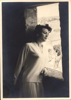 snapshot femme regardant par la fenêtre au balcon vers 1950