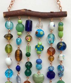 Jewelry for your patio!! This suncatcher/wind chime in blues and greens has a lock and key set and two bells. The glass beads/crystals are strung with copper wire from a piece of mesquite* Its very quite so it wont disturb neighbors.  This wind chime can withstand quite a bit of wind, rain, and snow but should be cared for during extreme weather. *Mesquite wood is 2 1/2 times stronger than oak and is dimensionally stable.  --Measures 4 by 12  --includes a copper chain for hanging which adds…