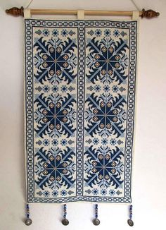 Beautiful Palestinian Bedouin embroidered wall hanging. The cross stitch embroidery is fully handmade by Bedouin women according to traditional geometric design. At its bottom youll find little hangers as signs of luck. This piece of art comes in Blue, Red or Green, on off-white