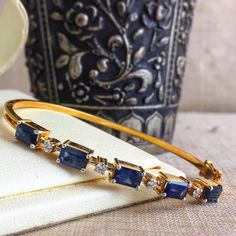 Striking hued blue sapphire bracelet designed with diamonds in between is a sleek and trendy piece of jewellery ! Sapphire Bracelet, Gold Bangle Bracelet, Sapphire Jewelry, Diamond Bangle, Blue Sapphire Necklace, Jewelry Design Earrings, Gold Earrings Designs, Bracelet Designs, Pendant Jewelry