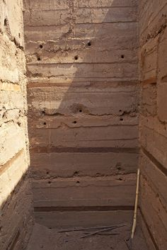 Rammed earth construction.  The holes are from the bolts that kept the forms together, Sam's Village (aka The Landirani Training Village) - face the strain