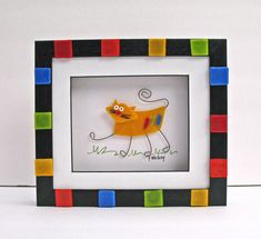 Whimsical sassy cat calico kitten picture made of yellow fused glass with stainless steel legs and tail. He hangs out in a black shadowbox frame