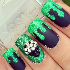Deadly poison themed glitter nail art design in green glitter polish and midnight blue matte polish with accents of a black skill and silver beads on top.