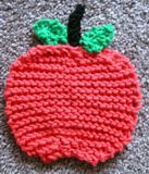 """Apple Shaped Coaster - - Knit ePattern,  A """"GREAT"""" teachers gift! Remember the days we took an apple to our teacher? Well, now your children can too, only apple will last! A great coaster for coffee, tea, and water bottles. Completed size is 4"""" by 4 ½"""". Use worsted weight cotton yarn for this simple shaping pattern. Make a yellow apple too! Everyone will want one. This coaster is on all our desks at Frugal Haus! Knitting needles, US# 10.  $1.75"""