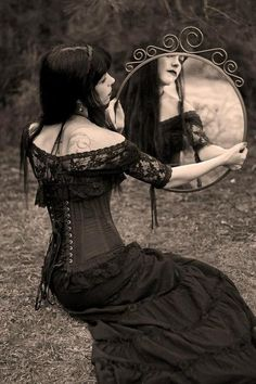 Dee comments:  A lovely romantic picture of a young goth holding a round mirror. I just love her wispy beauty and the tatoo on her exposed back.