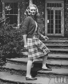 Model wearing plaid skirt and cardigan sweater representing the latest college fashions. US, 1943, Nina Leen