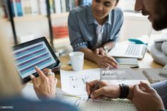 Stock Photo : Architects with blueprints using digital tablet in meeting