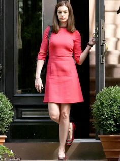 Different look: Anne Hathaway, 31, looked chic in a bright red Sixties style dress while f...