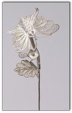 A sweet hairpin with a very lovely silver filigree butterfly and leaf flower. The butterfly is en tremblant so it moves over the flower.