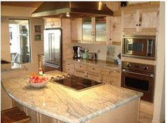 Quartz Countertops with cooktop on the island and double ovens.