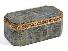 Boîte en labradorite, la monture du couvercle en or de trois couleurs. Modèle de forme rectangulaire à pans coupés. La bordure du couvercle à charnières est agrémentée d'une frise en or représentant des… - Fraysse & Associés - 24/11/2016