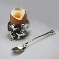 skull egg cup Gothic Skull egg cup. Crack open my head and eat my brains! That's one thing these egg cups might say to you if they could talk! The most original present ever. Silver Gothic spoon sold separately. We have been making these since 1995... Talk about ahead of our time. Choose from solid sterling silver, brass or aluminium.