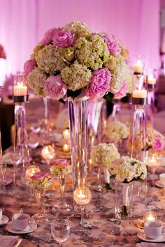 Large lush wedding centerpieces of hydrenga and peony(s). Low arrangements with roses and hydrengea. Sparkling lumina candle holders with floating candles for added elegance.