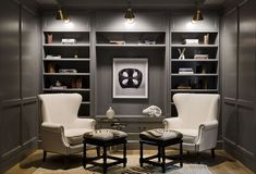 Gray Paneled Den Gray paneled den features a focal wall lined with gray built-in shelves and cabinets illuminated by Boston Functional Library Wall Lights. Hill Interiors, Office Interiors, Office Interior Design, Home Office Decor, Home Decor, Office Ideas, Library Wall, Library Design, Muebles Living