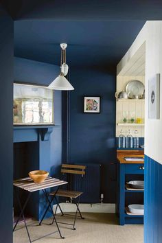 Painting the walls and ceiling in this kitchen in F&B Stiffkey Blue makes this corner cosy and inviting