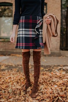 Preppy style for Fall: Plaid skir, over the knee boots, and a black long sleeve top.