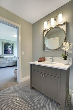 Grey bathroom cabinet paint color. Grey bathroom cabinet paint color suggestions. Grey bathroom cabinet paint color ideas. Grey bathroom cabinet paint color. This bathroom features gray walls, gray vanity and gray penny round floor tiles with dark grout. #Greybathroomcabinet #paintcolor