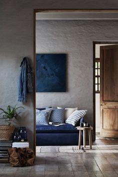 Rustikk og koselig stue med blå sofa og kunst på veggen