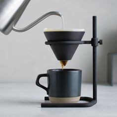 The brewer stand set intrigues with its rough look. It comes with a brewer stand made by casting, porcelain brewer, paper filters, server, a. Coffee Brewer, Coffee Cups, Coffee Maker, Coffee Set, Cafetiere Design, Coffee Equipment, Coffee Dripper, Coffee Stands, Home Coffee Stations