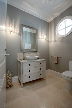 The bathroom features its own palette of neutral hues, with warm beige tile flooring and a dresser-style vanity that holds a large vessel sink.