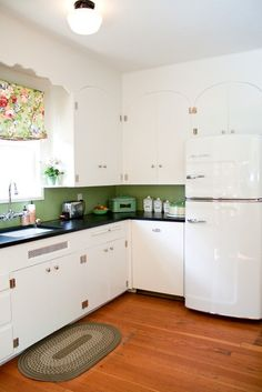 wood and white, retro fridge, scrolling above window, dark countertops are interesting; a vintage kitchen in a jadite green!