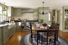 A farmhouse table with ladder-back chairs takes the place of an island in this 19th century home's newly remodeled kitchen. | Photo: Tria Giovan | thisoldhouse.com
