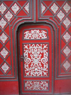 The decorations on this door remind me of frosting on a red velvet cake