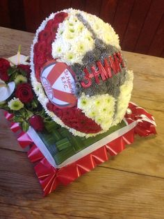 Rugby ball on base of woven leaves using two types of chrysanthemum head to define ball logos Funeral Tributes, Funeral Flowers, Chrysanthemum, Rugby, Leaves, Base, Logos, Logo, Chrysanthemums
