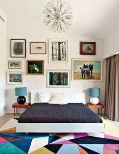 Lit king size avec couette gris. Tapis multicolore. lampes en noir et blanc. Tableaux accrochés sur le mur. Lustre hérissés.