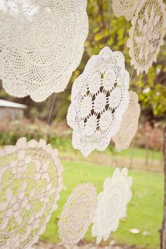 DIY shabby chic wedding backdrop with large lace doilies hung from tree branch.