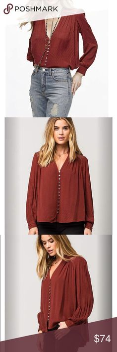 """Free People Canyon Rose Buttondown Red Shirt Features a spilt V-neck with a button front . Threaded gold embellishment at shoulders. Allover tonal stitch detailing . Button cuff long sleeves. Curved high -low hemline . 57% rayon, 43% modal .model is wearing small and she is 5""""9 .length is front 25 and back is 301/2 Underarm to underarm is 24 inches .color is red but looks like a burnt orange with gold threads Free People Tops Button Down Shirts"""