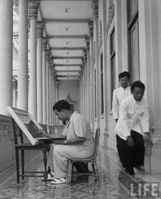 King Norodom Sihanouk of Cambodia painting in the hall terrace which is the background of the throne. Location:	Cambodia Date taken:	July 1952 Photographer:	Howard Sochurek