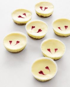 Raspberry-Heart Cheesecakes: What's better than a slice of cheesecake? Bite-size versions of the creamy, graham-cracker-crusted dessert. Whimsical hearts, shaped from tiny dollops of raspberry puree, make these the perfect treats to share with the people you love. —Martha Stewart Recipes