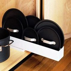 The Container Store > Pull-Out Lid Organizer Lids, cookie sheets, and baking pans stay organized and accessible with our clever Pull-Out Lid Organizer. It helps you sort out cramped, chaotic cabinets by using the often-wasted vertical storage space.: