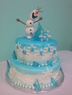 A frozen themed cake complete with hand sculpted Olaf and homemade ice candy
