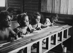 Photograph: School, Mornington Island, 1950. Courtesy of the State Library of Queensland and the community of Mornington Island.    In 1897 The Aboriginal Protection and Restriction of the Sale of Opium Act (Qld) allows the Chief Protector to remove local Aboriginal people onto and between reserves and to hold children in dormitories. Until 1965 the Director of Native Welfare is the legal guardian of all 'aboriginal' children whether the parents are living or not.