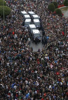 Madrid, Spain, Protesters surround police vehicles during anti-government demonstration.