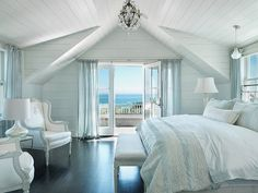 Beachy, rustic white wood paneling on walls opening up to gorgeousness view and sunroom, would look good with our black furniture...