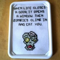 When life closes a door, it opens a window. Then zombies climb in and eat you. This zombie cross stitch sampler is set in a 3 x 5 inch photo frame. It has a magnet attached to the back, but can also be used as a hanging or free standing frame. This cross stitch sampler is 100% handmade by m...
