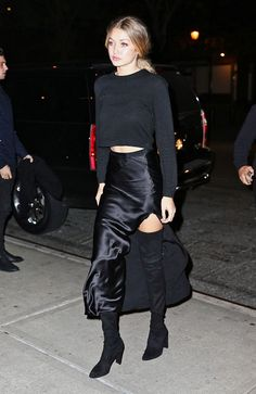 Gigi Hadid pairs thigh high boots with a high slit skirt for a cool girl night out look