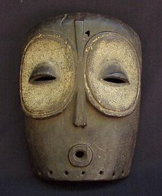 "WAGOMA-BABUYE FACE MASK - ZAIRE Face mask with round eyes, linear nose, and protruding mouth. Approximately 12 1/2"" x 9 3/4"". Wood, Pigment, Pierced for attachment. Mid century. FROM A PRIVATE AMERICAN COLLECTION. Kel-Mine."