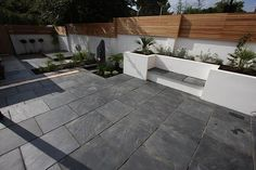 Blue Black Slate Paving in a contemporary urban garden. Looks fantastic against the crisp, white walls and  fencing.