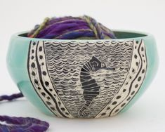 An etched seahorse is featured on this yarn bowl by Patricia Griffin in Cambria, Ca. It's handmade and has slot in back for yarn. Check them out online at patriciagriffinceramics.co