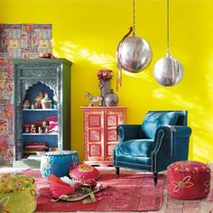 This is a gorgeous exotic interior with Indian and Moroccan influences. A Sunny Yellow wall is the background for this beautiful room with pops of efficiently placed turquoise accents. The fantastic silver ties the room together by drawing the eye to all the metallic pieces which gives depth to the room above the lounge chair. | Caption by Jenn Brown