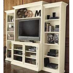 This is crazy expensive, but the idea is good -- set the TV-holder forward of narrow, shallow bookcases that flank it so there's space to work behind and the side bookcases hide that space and are easy to unload and move. Heeeyy .. I could put WHEELS on the side bookcases and then trim around the wheels to hide them! Would have to attach them to the main bookcase with a latch for stability. Hm.
