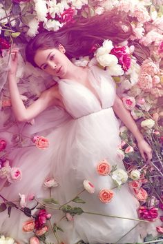 woman in tulle white dress lying on a bed of roses, so enchanting and beautiful
